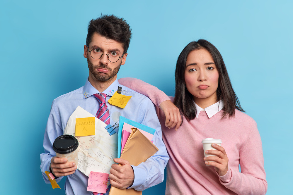 team-work-concept-two-displeased-tired-colleagues-prepared-financial-report-together-pose-with-coffee-go-look-sadly-camera-students-have-deadline-prepare-final-exam-university